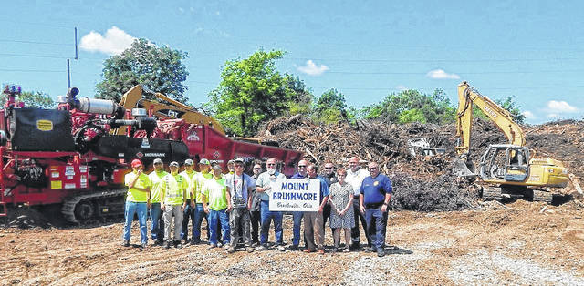 Ritter Plumbing employees and city of Brookville crews stand in front of a large pile of green debris, affectionately known as Mount Brushmore. After this photo was taken the debris was mulched and is available for donations. Donations for the mulch will be given to tornado relief funds.