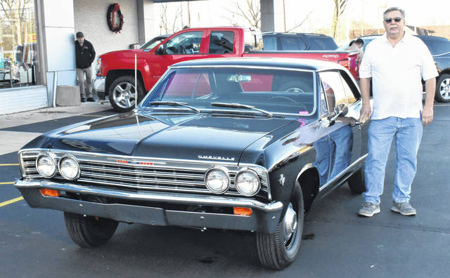 <strong>Richard McBride stands beside his fully restored 1967 Chevelle in front of the Reichard Chevrolet showroom.</strong>