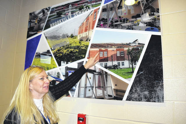 Brookville High School Assistant Principal Lynne Sayre-Nickell points to a photo display of the Memorial Day tornado damage. Brookville's FFA students organized a blood drive on Jan. 21.
