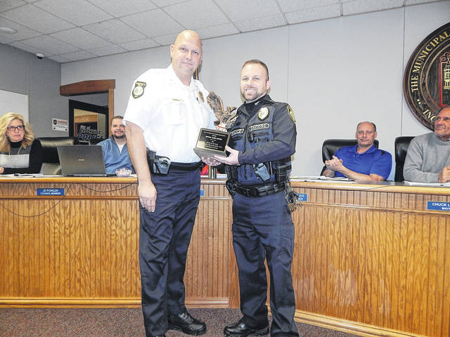 Newly appointed Brookville Police Department captain, Jason Jacobs (right) holds the Officer-of-the-Year trophy given to him by Brookville Police Chief Doug Jerome. Jacobs was not only sworn-in as captain at the Feb. 4 Brookville council meeting, he also received the Officer-of-the-Year award the same night.