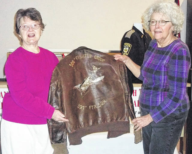 Doris West (l) and Wilma Schroeder examine a flight jacket worn by Paul Woolery in World War II. Woolery's family donated his flight jacket to the Randolph Township Historical Society.