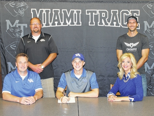 Caleb Wilt, seated, above, recently signed a letter of intent to attend the University of Kentucky, where he will run the high hurdles for the Wildcats. Wilt is flanked by his parents, Chip and Kim and joined by high school coach Brent Noes (standing at left) and trainer, Pat Woods.
