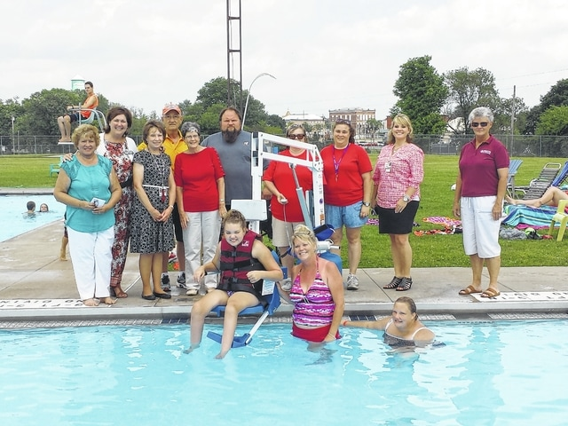 One of the children who makes use of the new Jeffersonville Community Pool chair lift addition provides a demonstration. Pictured here are various people who helped to bring the lift to the pool, including hospital trustees and employee, Sharon Gibbs from Help Me Grow, Jeffersonville council members and pool co-managers.