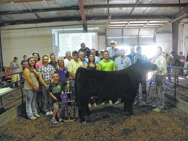Quinton Waits' Grand Champion Steer sold for $5,600 on Friday evening at the Fayette County Junior Fair Beef Steer Sale. Waits is pictured with fair royalty and buyers: (first row) Beef Queen Sydney Miller, Victoria Waits, Ashton Bain, (second row) Jeanette Dempsey of Kroger, Gus Bonham of Bonham Farm, Hallie Reiterman of Reiterman Feed, Josh Hagler of Seed Consultants, David Duff of OSC Farm Service, Doug Hauke of A-one Builders, (third row) Fair Queen Abbie Noble, Jason Humphrey of Fifth Third Bank, Mike Pell of First State Bank, Tim Fogt of Huntington Bank, Keith Tooill of McDonald's, Buck Minyo of Peoples Bank, Jared Hoop of Baxla Tractors, and Charlie Moorehead of Accurate Heating.