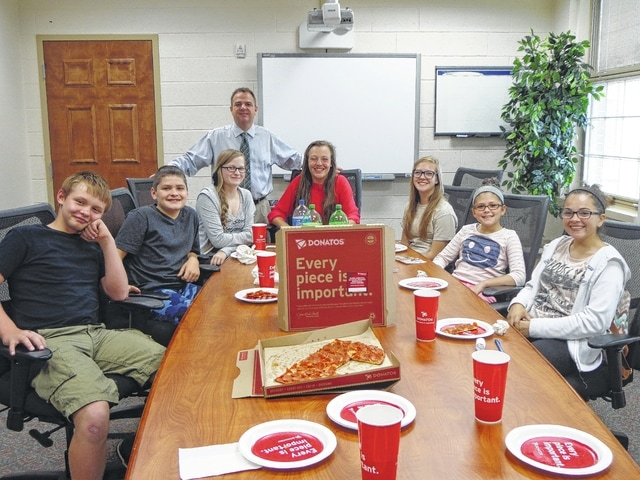 """Donatos recently provided pizza to these students at Washington Middle School as they celebrated """"Pizza with the Principals."""" This is in appreciation for their selection as Students of the Month for September. They are chosen by their teachers because of the outstanding example they set for their peers in such areas as academic effort, good work ethic, kindness to others, and service to their school. Pictured here (L to R): Levi Butcher, Mitchell Funderburg, Kiara Gilpen, Kearria Marcum, Brooke Reeves, Emily Coonrod, and Sydney Shadburn. Absent from the picture is Aaron Borden. Mr. Montgomery, assistant principal, is also in picture."""