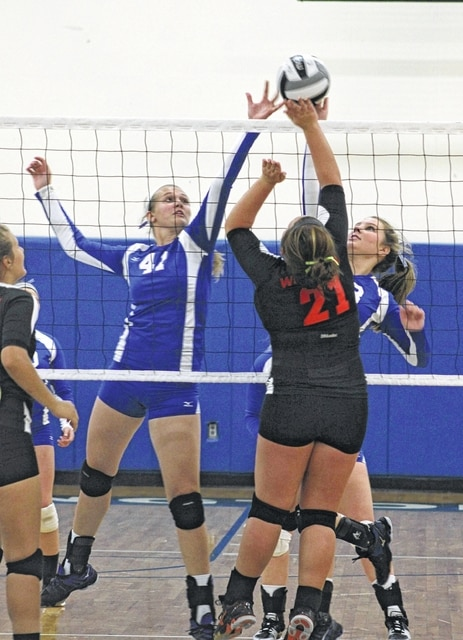Victoria Jones (41) and Madalyn Wayne make the play at the net for Washington during an SCOL match against Wilmington Tuesday, Sept. 8, 2015 at Washington High School.