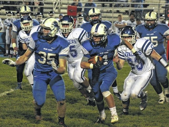 Washington sophomore Caleb Rice (4) carries behind the block of senior Mason McCane during an SCOL game at Gardner Park Friday, Oct. 23, 2015. Also pictured for Washington is Chad Moore (75).