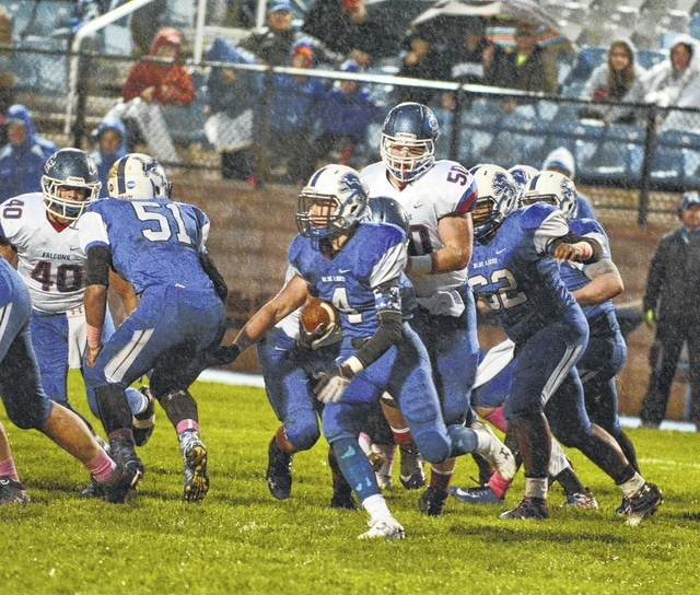 Caleb Rice (4) carries for the Blue Lions in a swirling, cold rain against the Clinton-Massie Falcons Friday, Oct. 2, 2015 at Gardner Park. Also pictured for Washington, Kameron Kearns (51) and Derrick Wade (62).