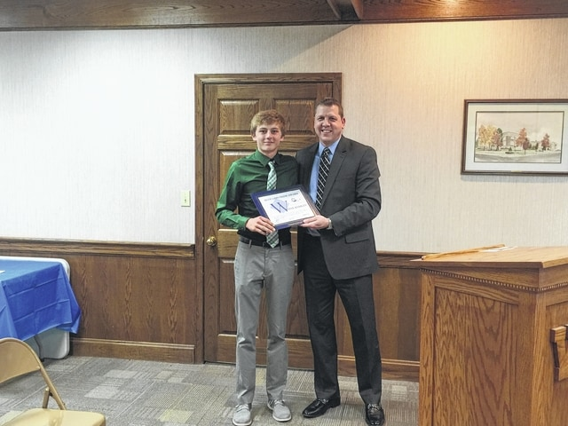 Max Knisley accepts his award from Washington City Schools Superintendent Matthew McCorkle during Monday night's school board meeting.