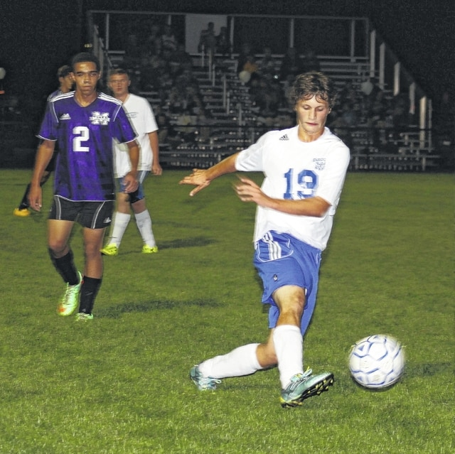 Washington Blue Lion senior Jakob Snyder kicks the ball away from the Washington goal area during an SCOL match against the McClain Tigers Tuesday, Oct. 6, 2015 at Washington High School.