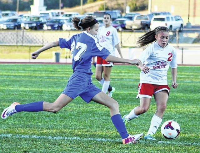 Savannah Davis (left) strides to the ball for Washington during a Division II Sectional tournament game at Hillsboro Tuesday, Oct. 20, 2015.