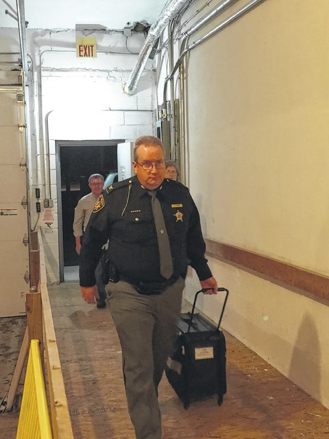 Fayette County Sheriff's Office Chief Deputy Sheriff Andy Bivens helps carry in ballots after the polls closed in Fayette County on Tuesday night.