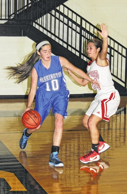 Washington junior Savannah Wallace (10) drives along the baseline during the season-opening game against Minford Friday, Nov. 20, 2015 at Paint Valley High School. Wallace is being guarded by Falcons' senior Emma Shepherd.