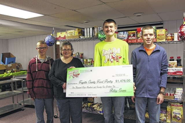 Riley Evans, Jingle Bell Jog director, presents Fayette County Food Pantry volunteers, Joey Pickelheimer, Joyellen Pickelheimer, and Joshua Pickelheimer with a check in the amount of $1,476.