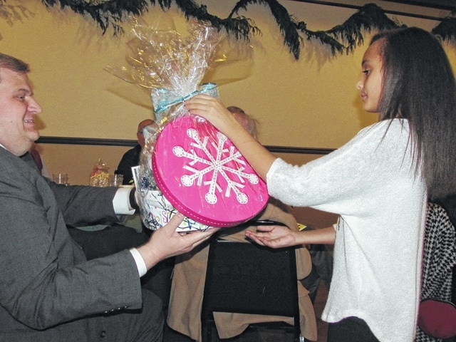 Peyton Black, at right, hands a gift basket to the high bidder, Kiwanis Club District 10W Lt. Governor Scott Lindsey, at left during the annual Washington Kiwanis Club Christmas Auction. Peyton, granddaughter of Kiwanians Kay and Jim Oughterson, joined President Lynn Hertler in showing the dozens of donated items to those attending the auction held at the Crown Room Banquet Center Monday night in Washington Court House. Travis Mick served as the auctioneer.