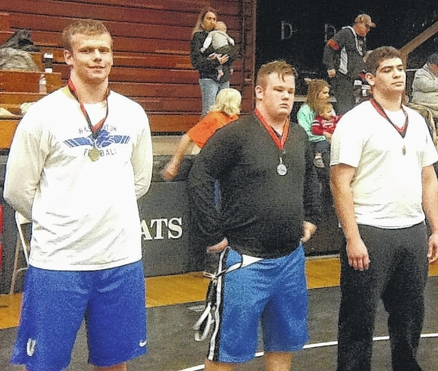Washington junior Trevor Hicks, above, left, is pictured after taking first place at 285 pounds at the Franklin Invitational Saturday, Dec. 5, 2015.