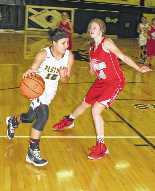 Miami Trace senior Harmonee Napier (12) drives against East Clinton freshman Kaitlyn Durbin during an SCOL game at Miami Trace High School Wednesday, Jan. 6, 2016.