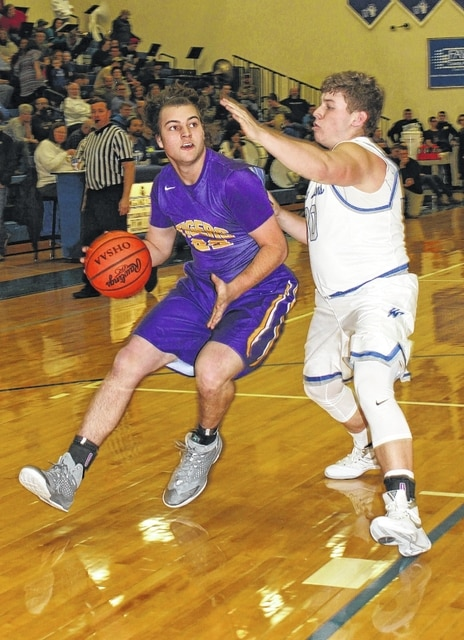 Washington Blue Lion senior Jacob Knisley, at right, defends against McClain's Randall Mischal during an SCOL game at Washington High School Friday, Feb. 12, 2016.