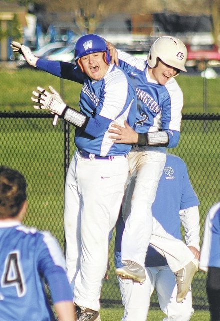 Brian Wilson (left) and Caden Cluxton celebrate after Wilson reached on an error that plated Cluxton with the winning run in a 4-3 victory over the Circleville Tigers Tuesday, March 29, 2016 at Washington High School.