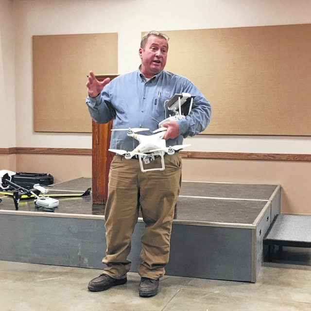 Gary Brock photo Jim Love, Light Robotics Manager and Herbicide Specialist for Beck's Hybrids, shows local farmers the DJI Phantom 2 UAV drone that can be used to help farmers gather information on their fields during the growing season. The drone pictured costs about $1,000.