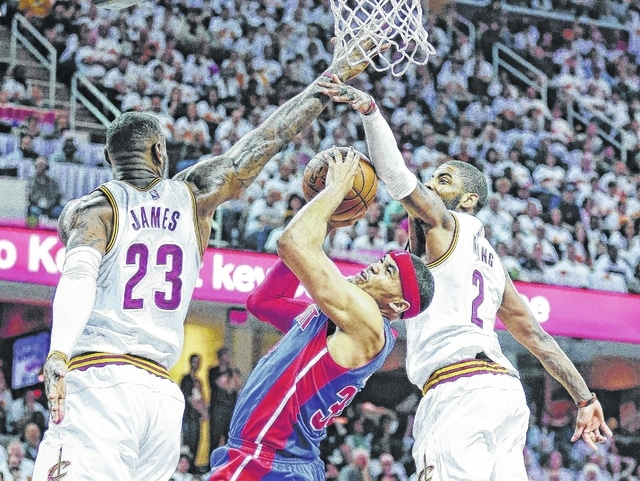 Detroit Pistons' Tobias Harris (34) drives to the basket against Cleveland Cavaliers' LeBron James (23) and Kyrie Irving (2) in the second half in Game 1 of a first-round NBA basketball playoff series, Sunday in Cleveland. The Cavaliers won 106-101.