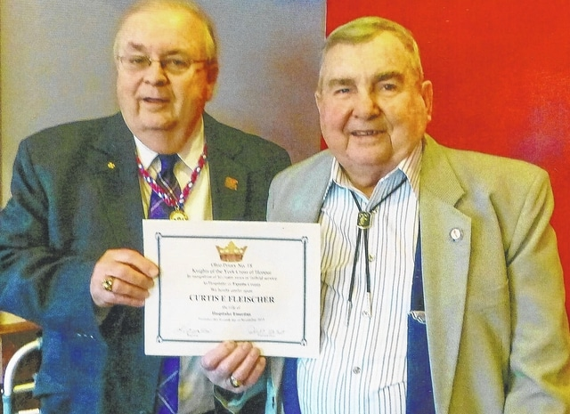 Norman Mick (left), Deputy for the 2nd District Ohio Priory Knights of the York Cross of Honour, presents former Miami Trace High School Principal Curtis E. Fleisher a certificate in recognition of the Ohio Priory naming him Hospitaler Emeritus for Fayette County.