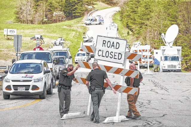 Authorities set up road blocks at the intersection of Union Hill Road and Route 32 at the perimeter of a crime scene Friday in Pike County, Ohio. Eight members of the same family — seven adults and one 16-year-old — were killed at four locations by a killer who used gunshots to the head. Three children, ages 4 days to 3 years, survived the killings. The attorney general's office said a dozen Bureau of Criminal Investigation agents had been called to Pike County, an economically struggling area in the Appalachian region 80 miles east of Cincinnati.