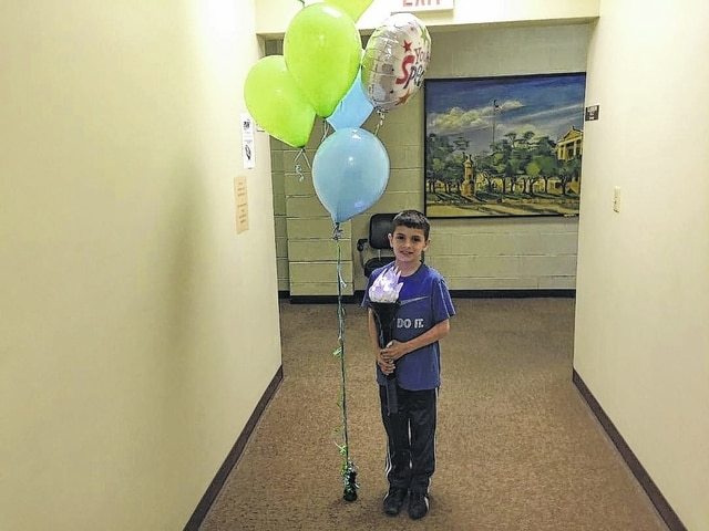 """Ian Sanchez, now 10, received a heart transplant when he was only 3-months-old. He continues to thrive and his life was celebrated Wednesday during a presentation at the Washington C.H. BMV. Here, he holds the """"Torch for Life."""""""