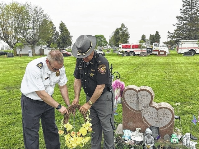 Jefferson Township Fire Chief Aaron Hauer and Fayette County Sheriff Vernon Stanforth placed a wreath Wednesday at Mackenzie Branham's gravesite. Authorities are still searching to solve the case of the arson fire that killed Mackenzie 10 years ago.