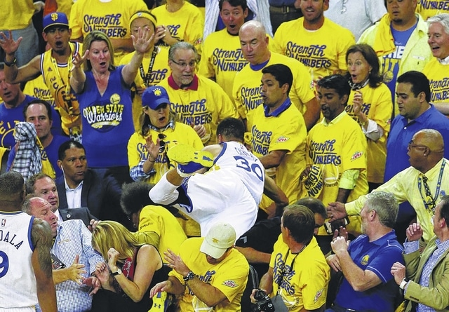 Golden State Warriors guard Stephen Curry (30) falls over a row of fans while chasing a loose ball during the first half of Game 2 of the NBA basketball Western Conference finals against the Oklahoma City Thunder in Oakland, Calif., on Wednesday.