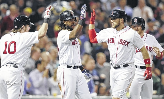 Boston Red Sox's Travis Shaw, second from right, is congratulated after his three-run home run off Oakland Athletics pitcher Daniel Coulombe during the fifth inning at Fenway Park in Boston on Tuesday. The Red Sox won 13-5.