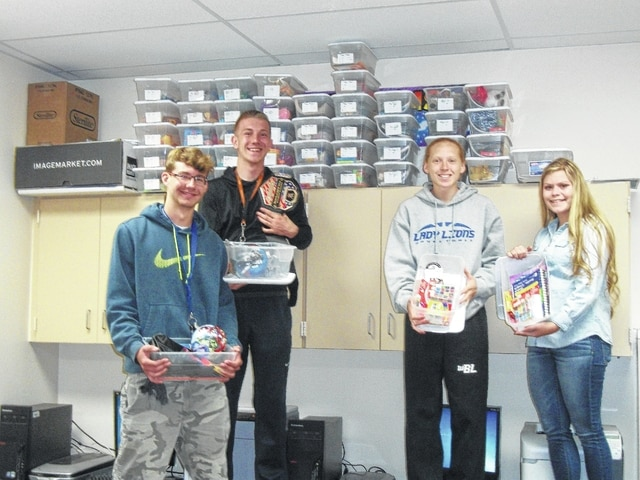Branton Mitchell, Hunter Sever, Alexis Gray and MaryKate Van Dyke, all members of the Washington City Schools High School DECA Club, in front of their 50 boxes filled with toys to be donated to Children's Hospital.
