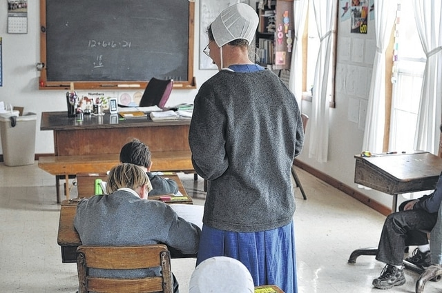 A teacher helps a student inside the Amish school. Photography has become more tolerated by the Amish in general over the past 25 years.