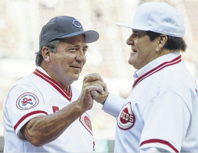 Former Cincinnati Reds players Pete Rose, right, and Johnny Bench clasp hands as Rose is introduced for a ceremony to honor the 1976 World Series champions before the Reds' baseball game against the San Diego Padres on Friday in Cincinnati. The Padres spoiled the opener with a 13-4 defeat of the Reds.