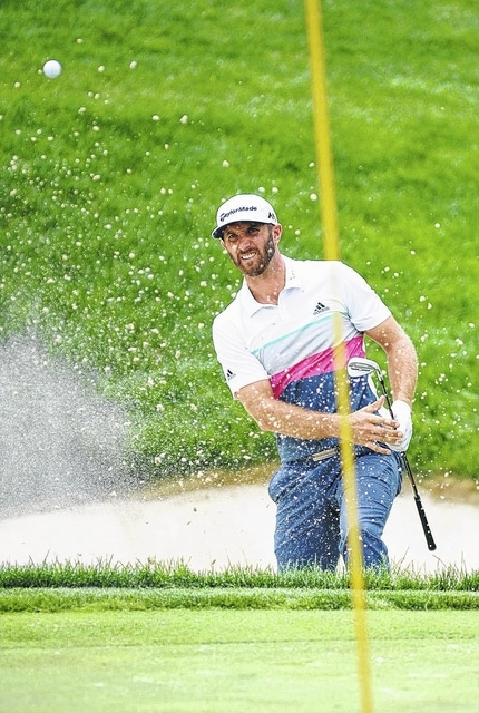 Dustin Johnson chips out of a green-side bunker on the way to bogeying the 17<sup>th</sup> hole at The Memorial Tournament Thursday. He shot an 8-under 64 in the opening round.