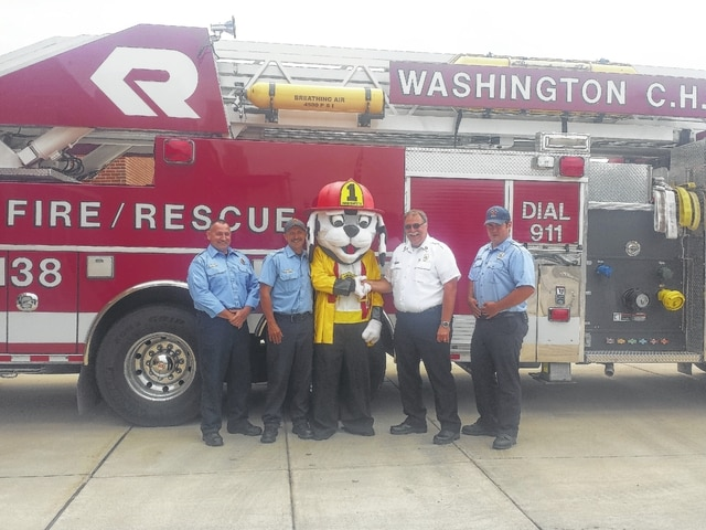 The Washington Court House Fire Department showed off the new FirePup as part of their fire safety education in collaboration with National Fire Safety Council, Inc. and the community. In cooperation with the department, citizens and businesses will help the department provide an assortment of fire safety educational materials to local children. These materials are distributed in our schools, at safety fairs, through public presentations, and to children when they visit the fire stations. Pictured are WFD Firefighters, FirePup and WFD Chief Tom Youtz.