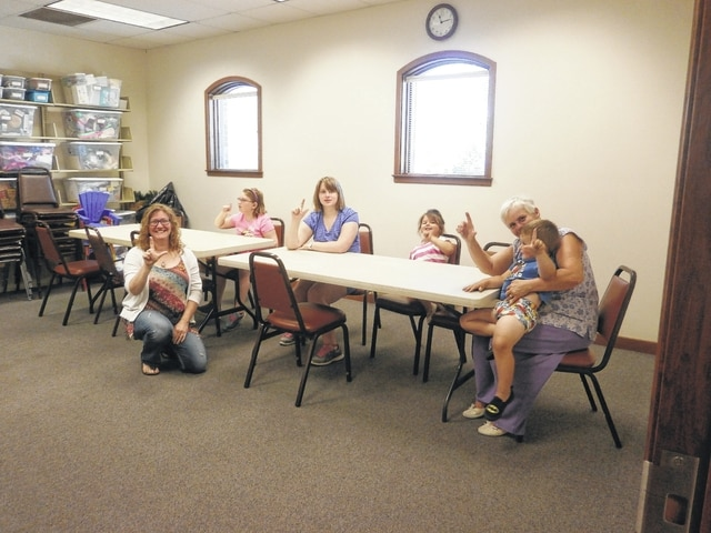 """Jenny Benedetti, local sign language interpreter, taught sign language basics at Jeffersonville Branch Library to many participants. Here, some are shown signing """"Library."""" How appropriate."""