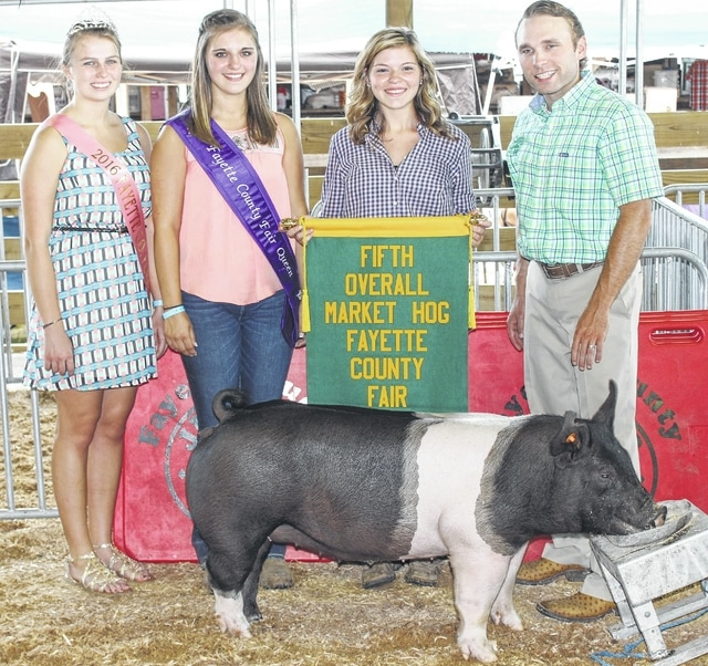 Kendal May (holding banner) won the fifth overall market hog prize Wednesday at the market hog show. Pictured with Kendal are Fayette County Pork Queen Hannah Casto, Fayette County Fair Queen Bethany Reiterman, and the judge of the show, Nathan Day.