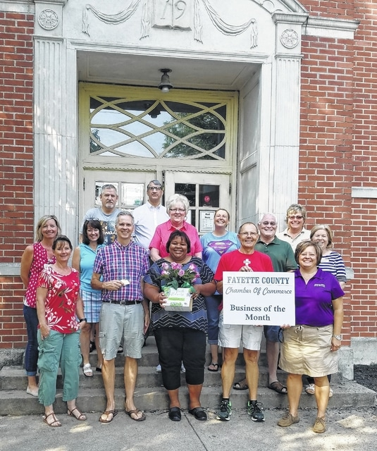 Free Store Director, Chiquita Nash holds the flowers presented to The Well at Sunnyside for being the Fayette County Chamber of Commerce Business of the Month. Nash is flanked by The Well's board members and the Chamber Ambassador team.