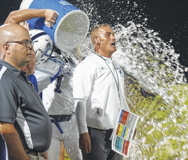 Washington head coach Chuck Williamson gets a celebratory drenching of ice water at Northridge High School as the Blue Lions made his debut a victorious one.