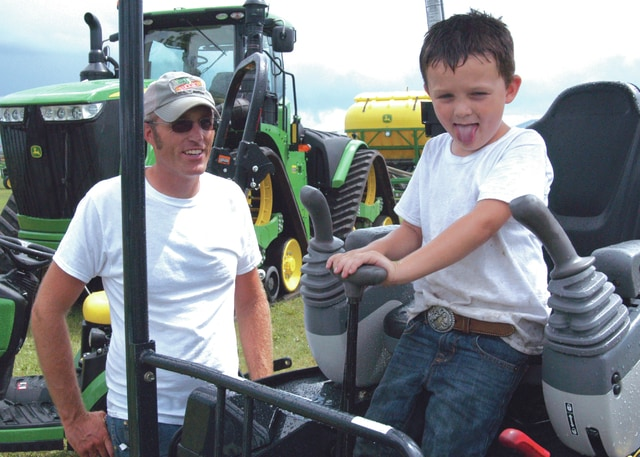 """Young Andy Waddle of Washington Court House enjoys """"driving"""" the farm equipment on display while his father Clayton looks on at the Southwest Ohio Corn Growers and Fayette County Agronomy Day held Tuesday at the Fayette County Airport and Demonstration Farm."""