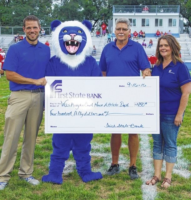Jon Creamer (left), Washington High School athletic director, and the Blue Lion mascot, accept a donation from First State Bank representatives, Mark Richards, manager, and Karen Cassidy, office manager.