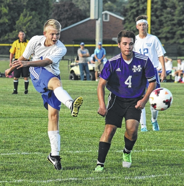 Jack Luebbe fires a shot on goal for the Blue Lions, defended by Brandon Goddard (4) of McClain during an SCOL match Thursday, Sept. 8, 2016 at Washington High School.