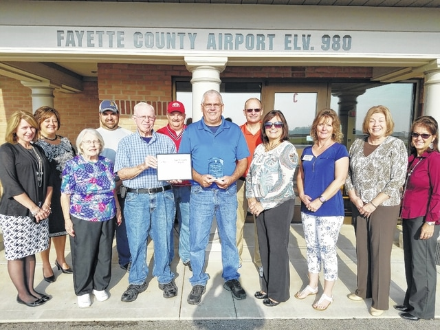 Surrounded by Chamber Ambassadors and members of the Fayette County Pilot's Association, retired airport manager Tom Esper (left) and current manager Jerry Van Dyke, hold the plaque and certificate from the Fayette County Chamber in honor of the airport's 50th anniversary. Esper served over 30 years while Van Dyke has been on the job for five.
