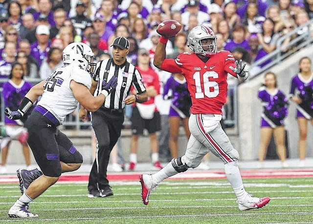 Ohio State QB J.T. Barrett (16) makes a throw as he is chased by Northwestern Alex Miller (95) at Ohio Stadium on the campus of The Ohio State University October 29, 2016.