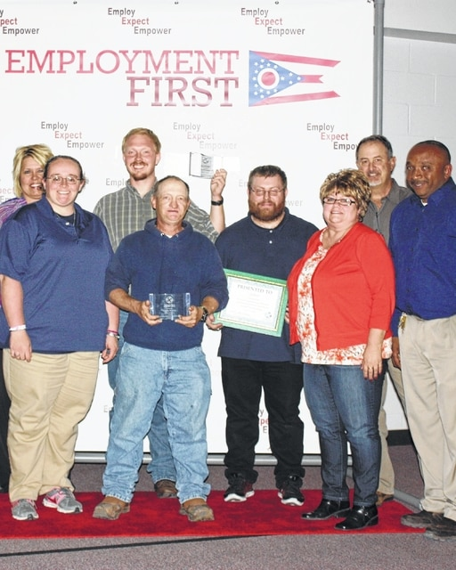 Walmart employees (left to right, front) Jenn Taylor, HR; Donnie Butcher; Josh Maddux; Ronda Bryan, HR; and Mike Powell, store manager. Second row, Betty Reisinger, community resource director at FCBDD; Chad Richards; Josh Maddux; and Mark Heiny, board member at FCBDD. Donnie Butcher is holding the award he received in recognition of 14 years of competitive community employment at Walmart. Chad Richards received an award in recognition of two years of competitive community employment at Walmart. Josh Maddux is a new hire at Walmart.