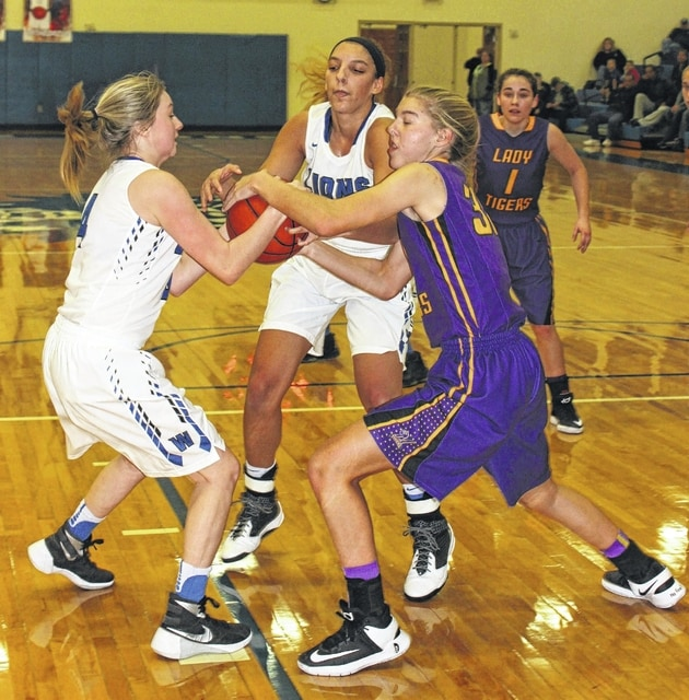 Washington's Bre Taylor (left) and Hannah Haithcock battle for a loose ball against a player from McClain during an SCOL game at Washington High School Saturday, Dec. 10, 2016.