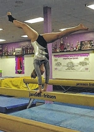 Victoria Waits executing a back walkover on balance beam.