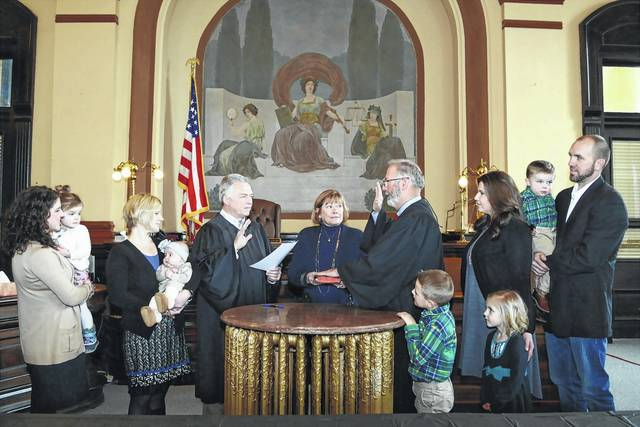 Fayette County Court of Common Pleas Judge Steven Beathard was sworn in by Probate Judge David Bender Feb. 9 for his third and final term. Judge Steven Beathard's current and final term will expire in six years in 2023. Beathard studied at the Ohio State University where he earned an undergraduate degree in animal science. He studied law at the University of Toledo College of Law, completing his law degree in three years. For 27 years, Beathard was a private practice attorney in Madison County, where he served as the London City Law Director, and opened a law practice in Washington Court House. Beathard, a Republican, was first elected in 2004 to serve as the Fayette County Court of Common Pleas Judge. He won re-election, unopposed, in 2010. Beathard, who has an interest in history and renovation, initiated work to preserve and update the 169-year-old Fayette County Courthouse. The work took 10 years to complete and included restoring the murals and frescoes on the third floor, where the court of common pleas is located. The courthouse is registered on the National Register of Historic Places. Beathard is pictured here during his swearing-in ceremony. His wife Leanne, pictured in the center, and family surround him during the ceremony.
