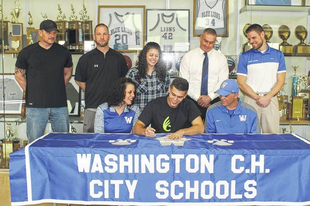 Kameron Kearns, seated, middle, Washington High School senior, signs a letter of intent Thursday, March 9, 2017 to attend Wilmington College where he will continue his education and his football career. He is flanked by his parents, Grace and Robbie and also joined by (standing, l-r); former junior high coach Scott Coe, former varsity coach Corey Dye, his sister, Jordan; current varsity coach Chuck Williamson and the school's athletic director, Jon Creamer.